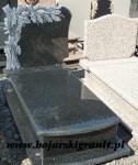 121z Nagrobek pojedynczy z ciemnego kamienia z rzeźbioną tablicą - liście drzewa dębowego.